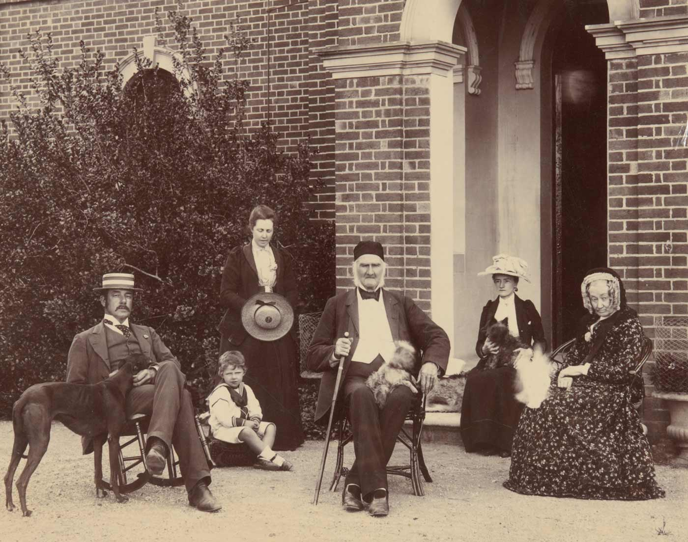 Black and white photo showing two men, three women and a child outside a brick building. The man at centre holds a walking stick and has a small dog sitting on this lap. The other man sits in a rocking chair, with the head of a kangaroo dog resting on his lap. To his right is a small boy in a sailor suit, and a woman, standing, who is looking down. The women seated, far right, both hav animals resting on their laps.
