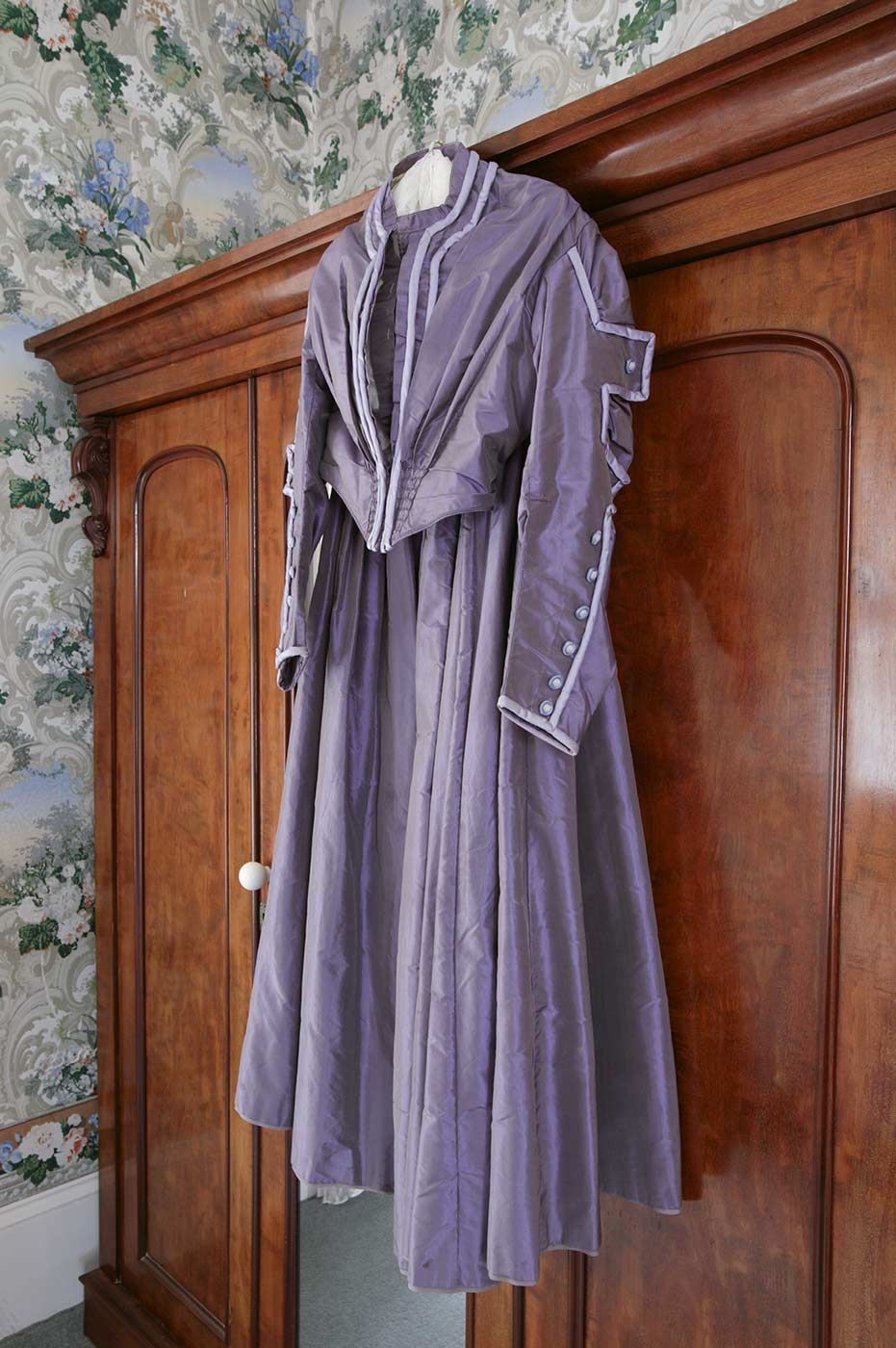 Purple period dress hanging from a wardrobe. - click to view larger image