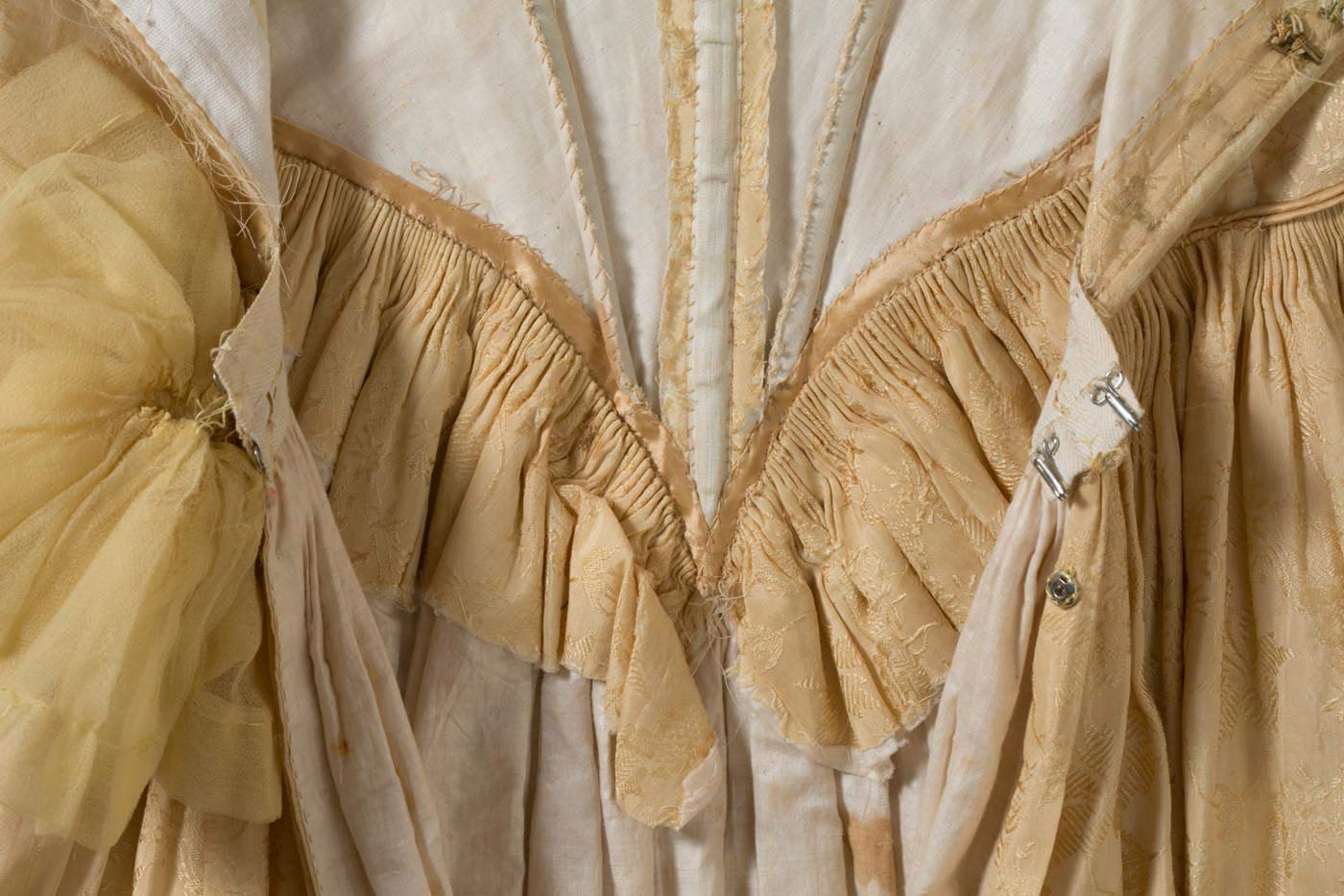 Cropped image of a silk dress with fine pleating at the centre back of the dress. - click to view larger image
