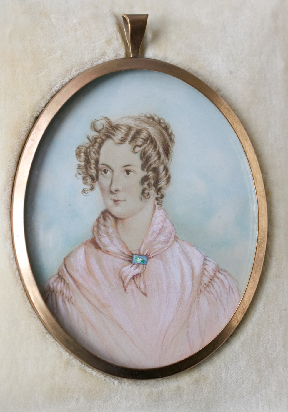 Miniature portrait in an oval frame of Ann Deane as a young woman showing ringlets around her face and a head band at the back of her hair, wearing a pink coloured top with puff sleeves and a necktie collar in the same colour held together with a blue clasp with white design in the centre front. - click to view larger image