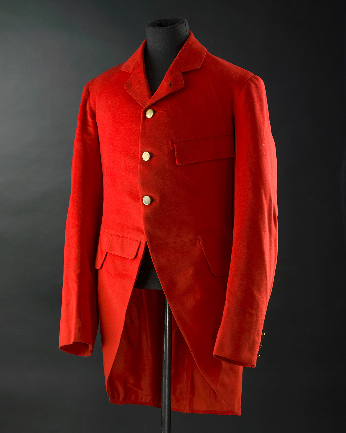 A red wool cut away jacket with tails otherwise known as hunting pinks. It has 3 brass shank buttons at front opening and 3 buttons on each cuff. It is fully lined in red cotton. The sleeves are lined in white cotton with blue stripe. The jacket has machine quilted underarm lining and a back vent with 2 brass buttons at top. It has four pockets on front with flaps. - click to view larger image