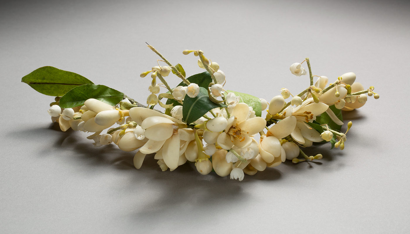 A strip of cream coloured fabric and wax or plastic flowers with green leaves. The flowers are on a curved piece of wire and are a little dirty.