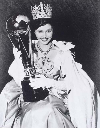 Miss Australia 1960, Rosemary Fenton holding the Miss Australia trophy on her lap, wearing the crown, robe and long white gloves - click to view larger image