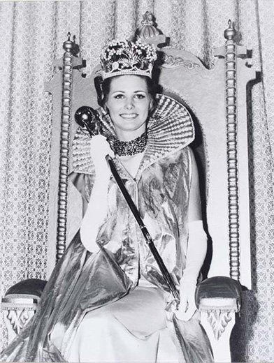 Miss Australia 1970, Rhonda Iffland sitting in the winners throne, holding the sceptre wearing the crown a long, gold, frill-collared, sleeveless cape and long white gloves - click to view larger image