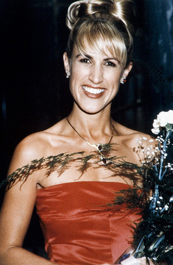 Miss Australia 1997, Tracy Secombe wearing a red strapless dress, holding a bouquet of flowers - click to view larger image