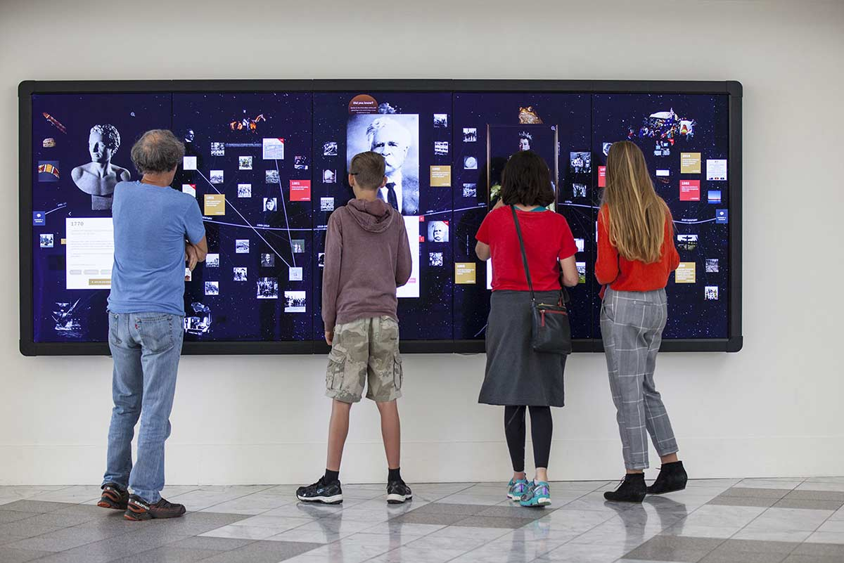 Visitors interact with the Digital Discovery Wall inside the Museum's Gandel Atrium.