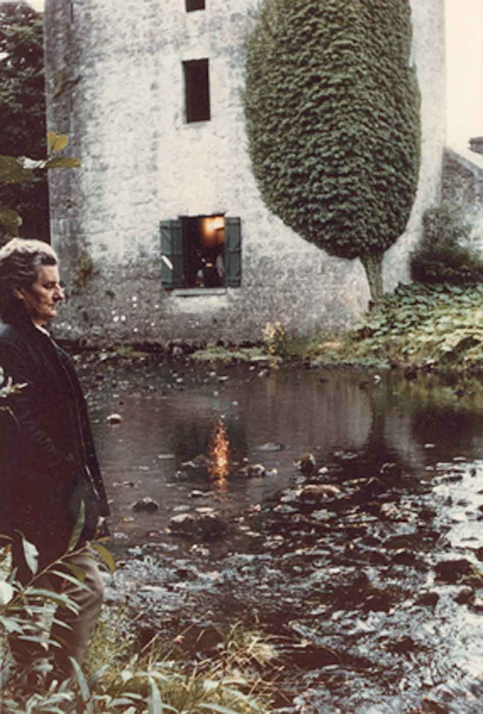 Faded photo of an elderly man standing by a large brook overlooked by a tall old stone building. - click to view larger image