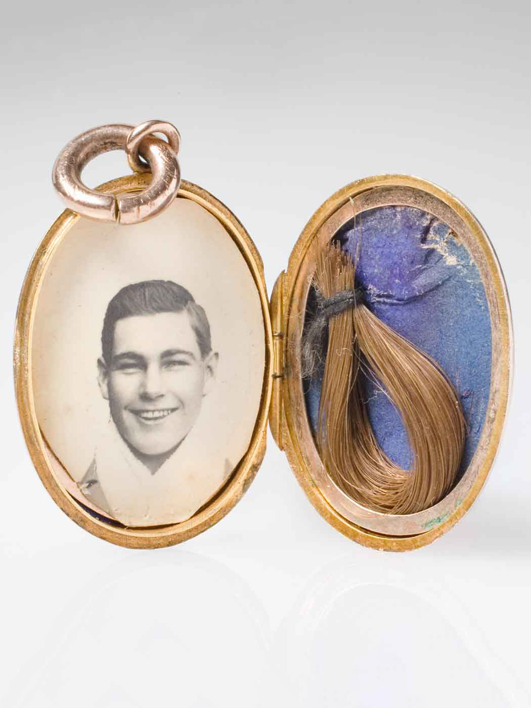 Open locket containing a black and white photo of a young man and a lock of hair. - click to view larger image