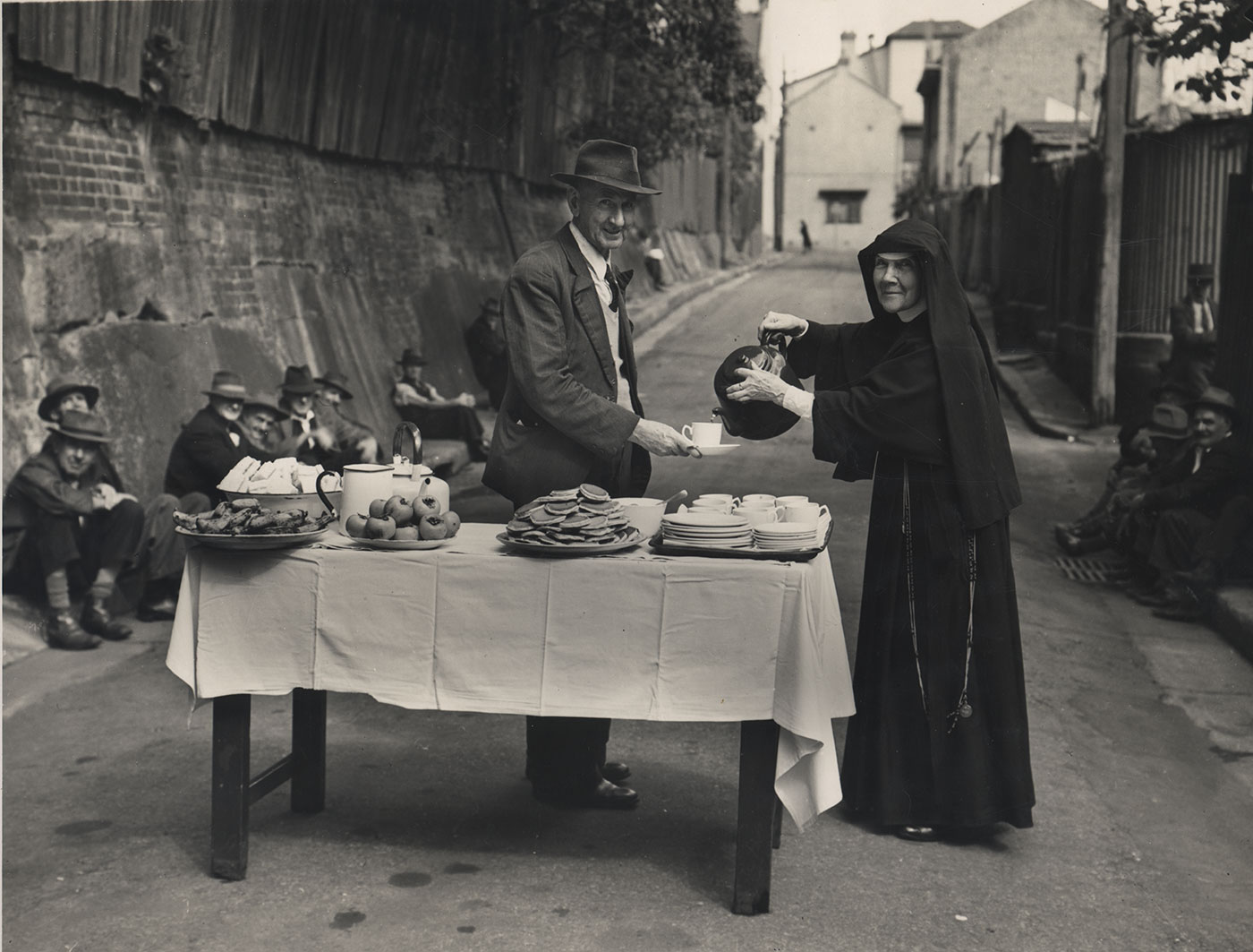 Black and white photo of a nun serving food and hot beverages to a group of men on the street. - click to view larger image