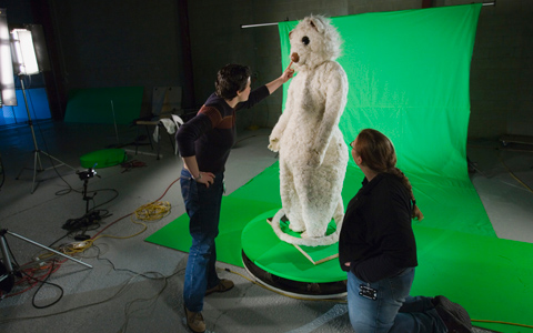 A human-sized white-coloured possum costume on a free-standing frame is posed in front of very bright green background fabric. Two people, one on either side of the costume have their backs to the camera, the person on the left is reaching towards the costume's nose.
