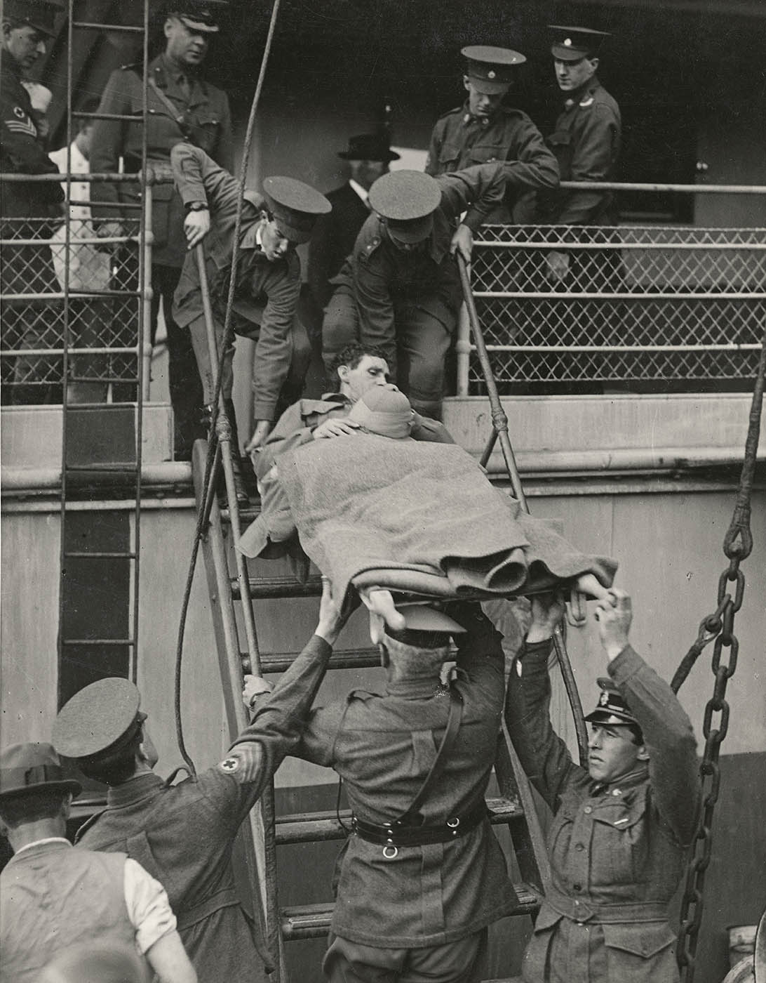 A soldier on a stretcher is being lifted by other soldiers disembarking from a ship. - click to view larger image