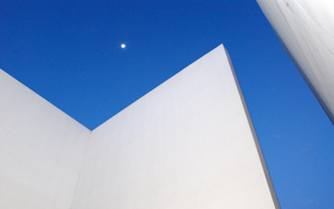 Abstract image of one of the Museum building's architectural features. White walls zig zag across the image frame with deep blue sky in the background.