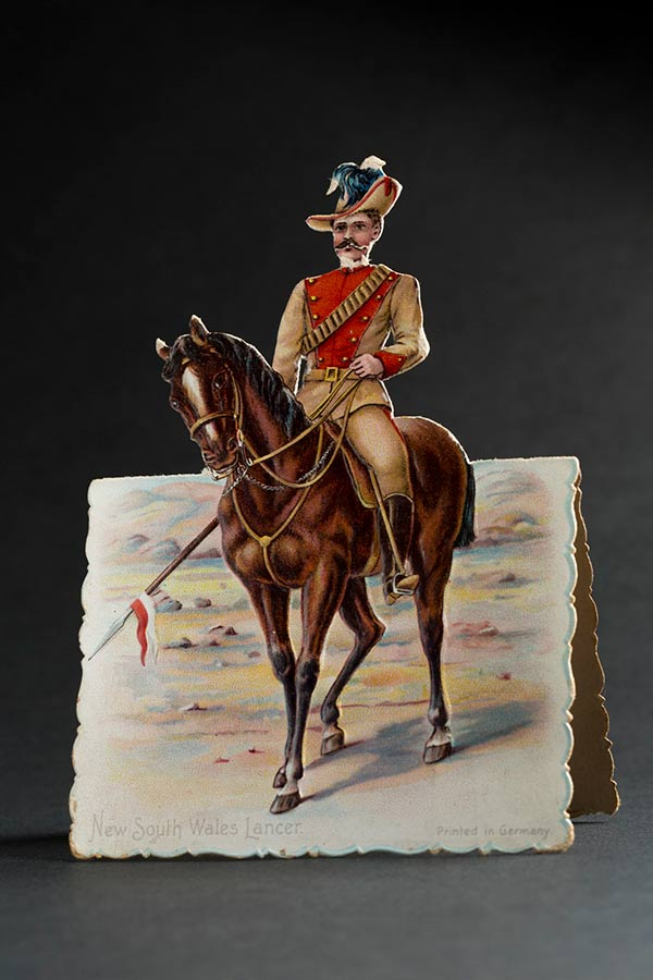 A card with a soldier on horseback in a desert scene. 'New South Wales Lancer, printed in Germany' is printed at the bottom of the card. - click to view larger image