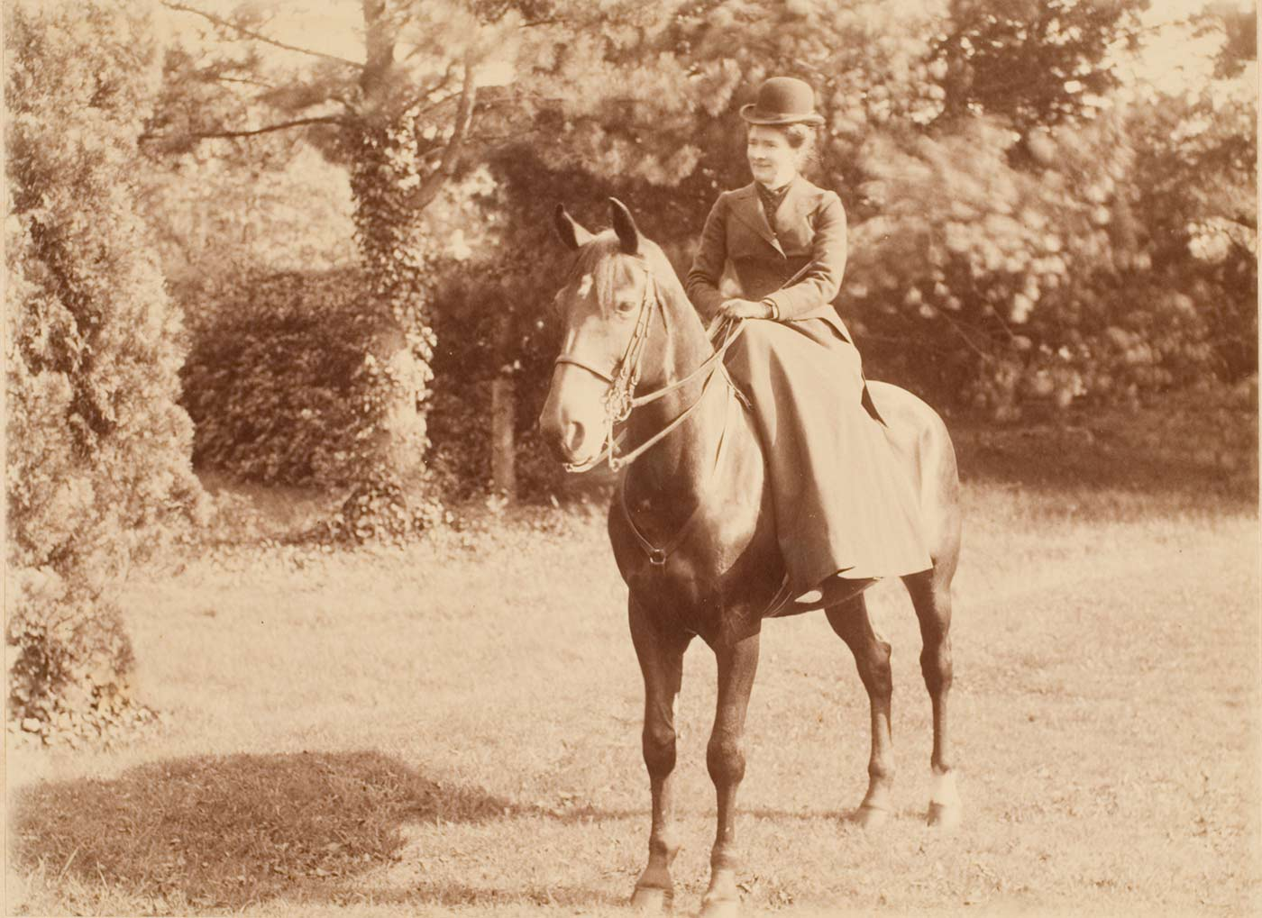 Sepia photo of a woman sitting side-saddle on a horse. She wears a long skirt, tailored jacket and hat.