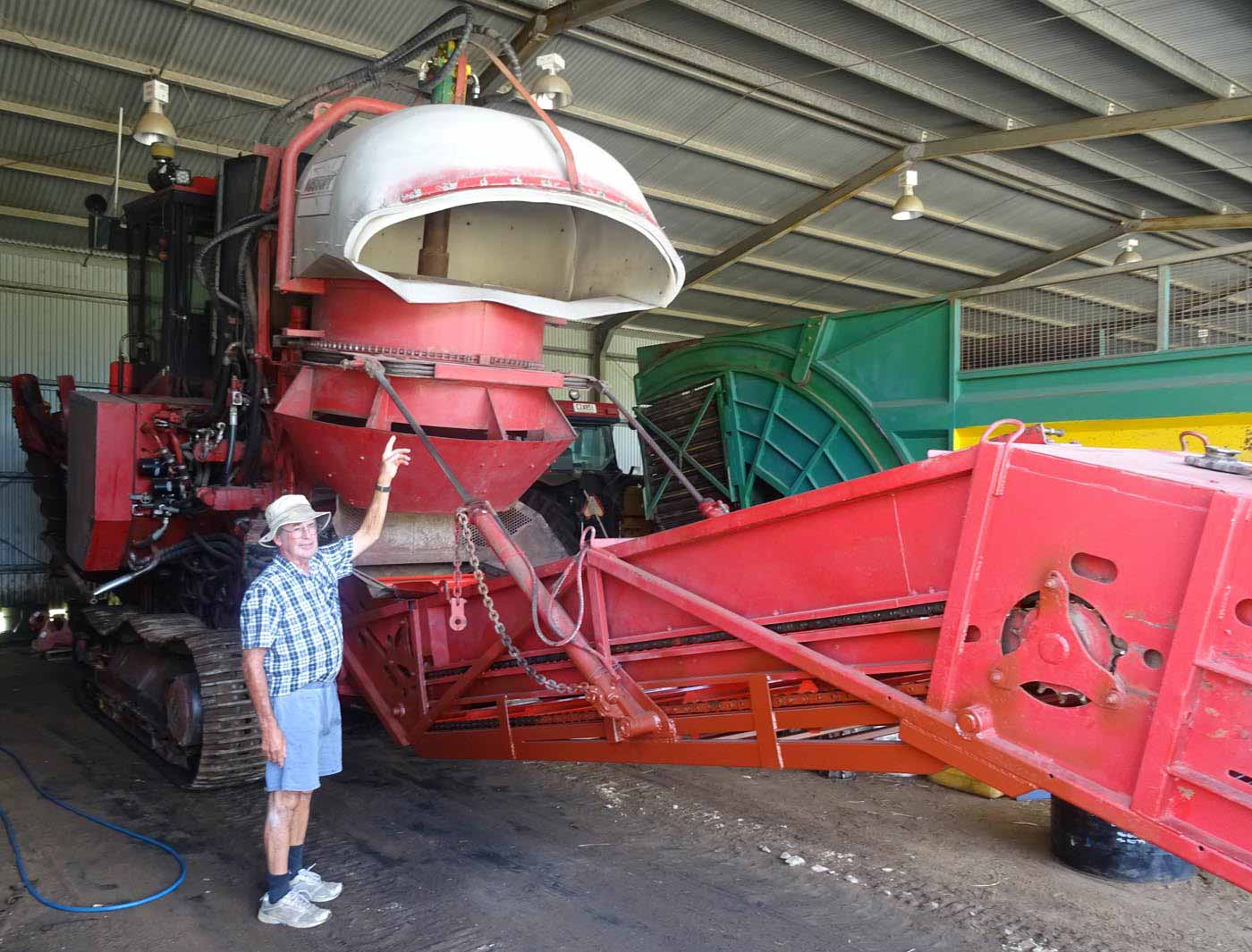 A colour photo of a man standing in front of a large red and white farm machinery. - click to view larger image
