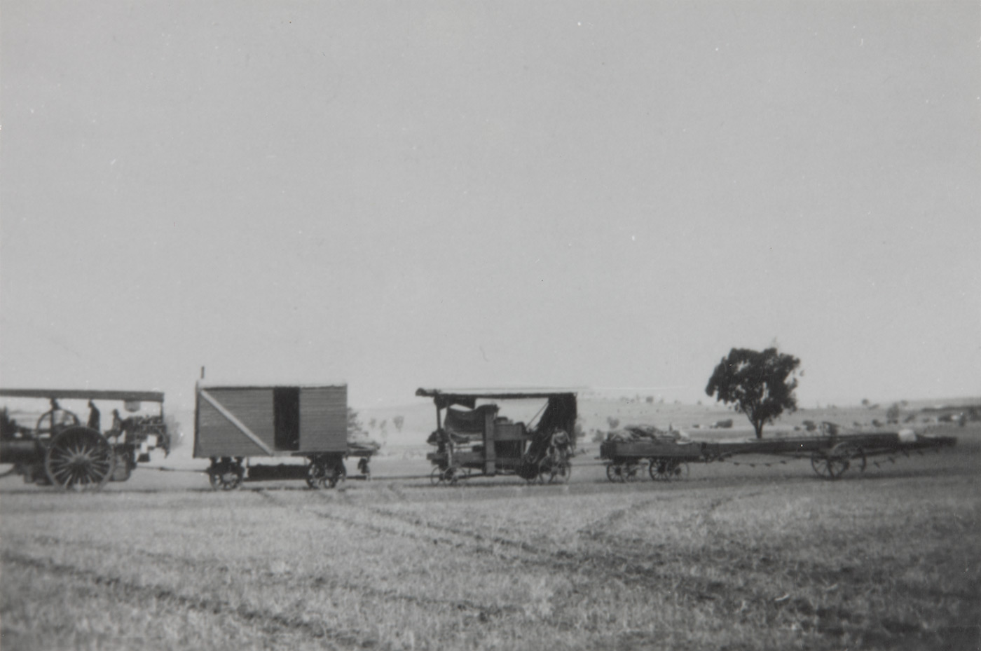 A steam-powered vehicle pulling two carriages and a trailer. - click to view larger image