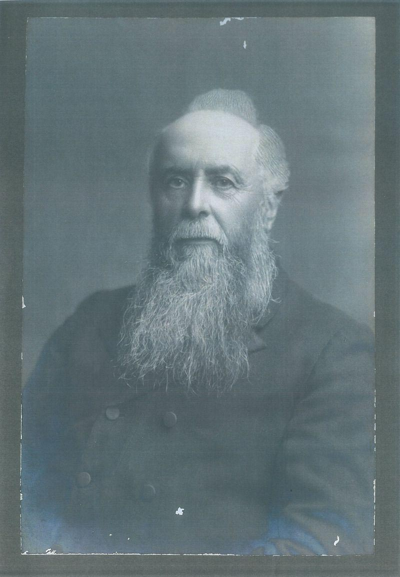 Black and white photo of a portrait of a man with grey hair and long beard, wearing a double-breasted coat. - click to view larger image
