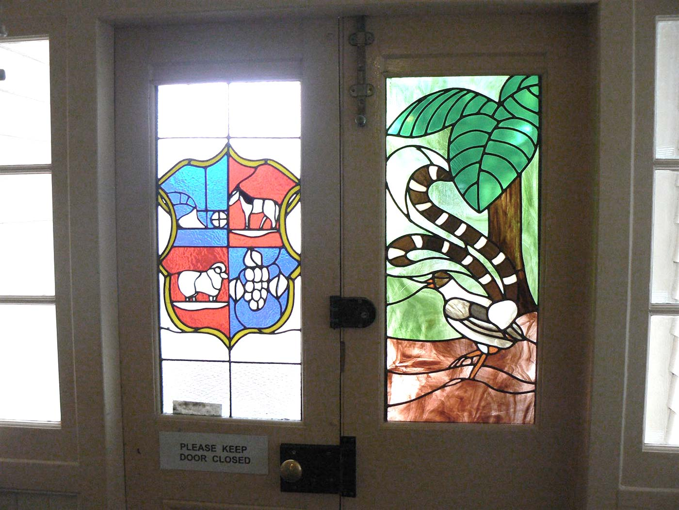 Leadlight windows featuring a design in the style of a coat of arms on one side and a forest scene with a bird on the other.