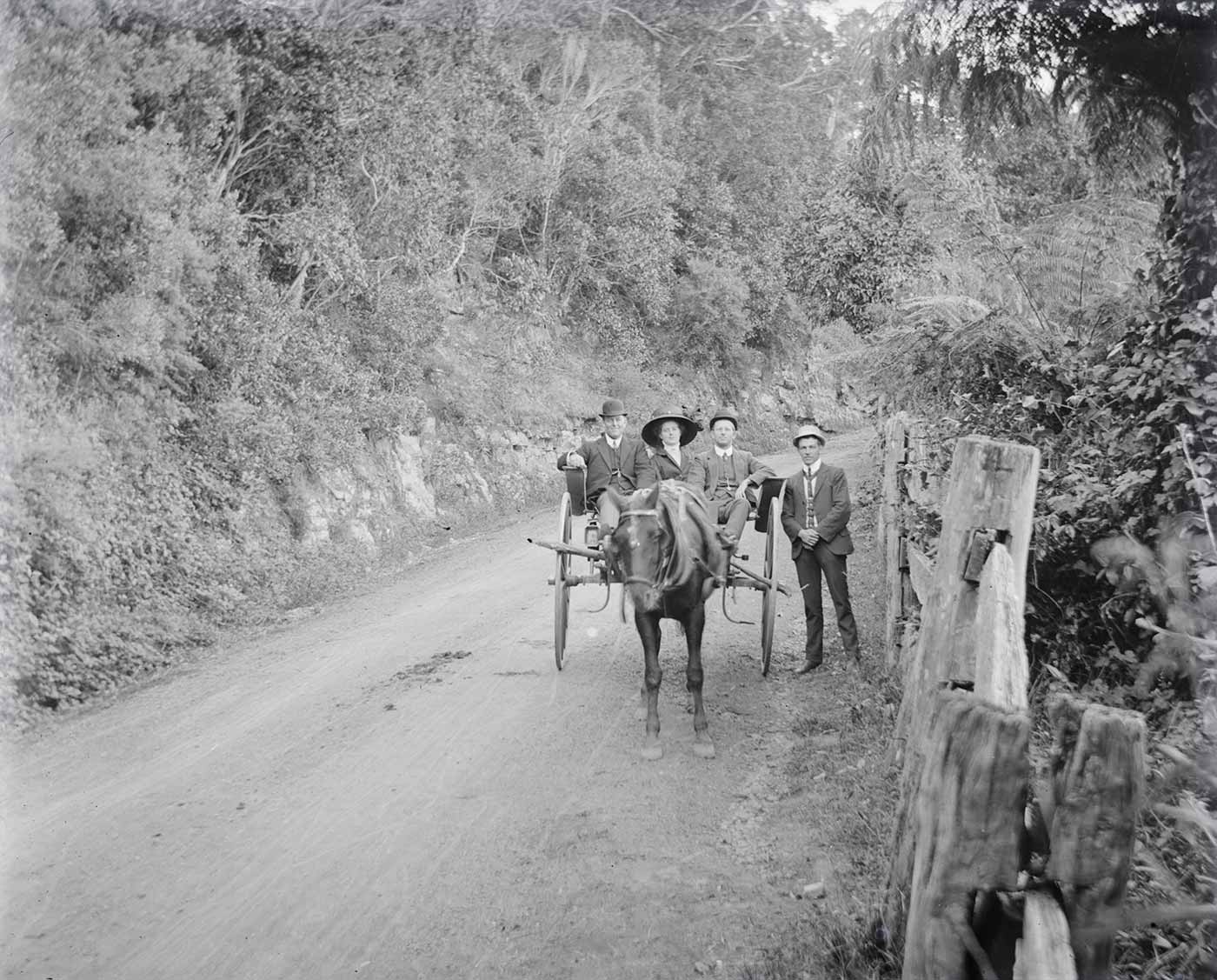 A photographic glass plate negative showing a horse-drawn buggy on a dirt road. There are two men and a woman wearing a large brimmed hat riding within the buggy, while another man is standing outside beside one wheel. All the men are wearing three-piece suits and hats. - click to view larger image