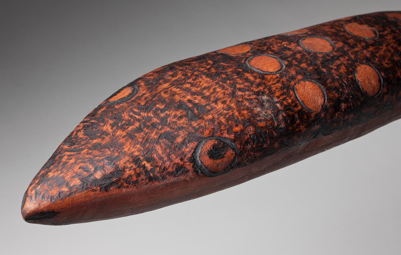 Closeup of face of Ngintaka sculpture carved from red gum timber. - click to view larger image