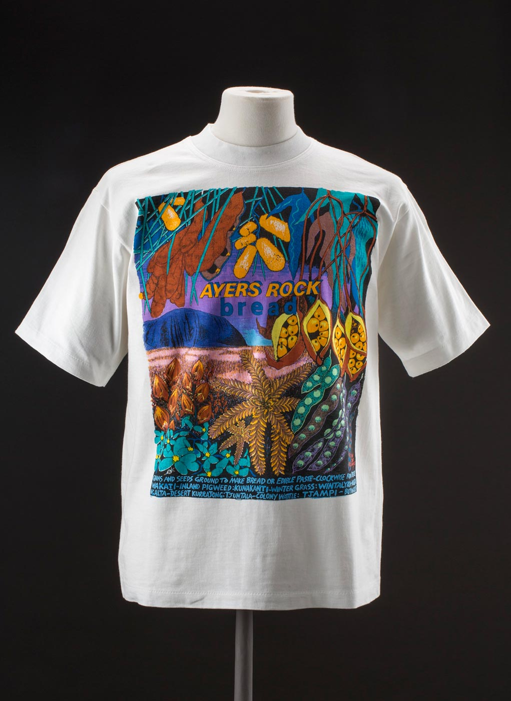 Depicted on the T-shirt is a brightly coloured landscape featuring native plants and seeds in foreground, Uluru / Ayers Rock in background and text above