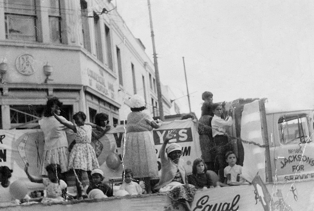 Black and white photo of campaigners on a float fixed with protest banners.