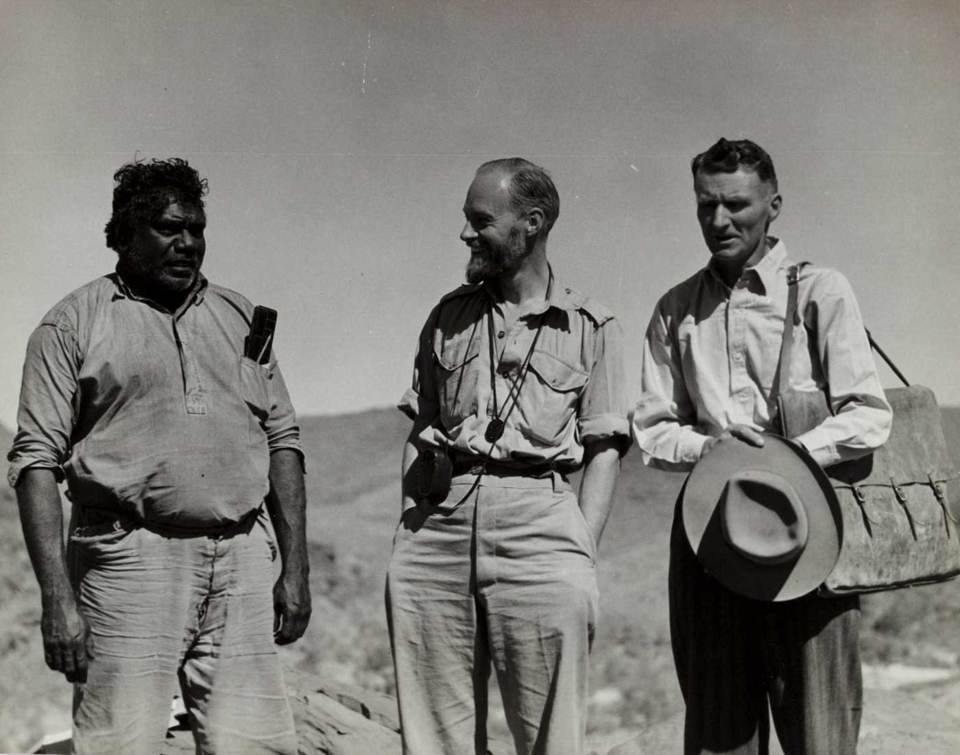 Black and white photo of three men standing in an arid landscape.