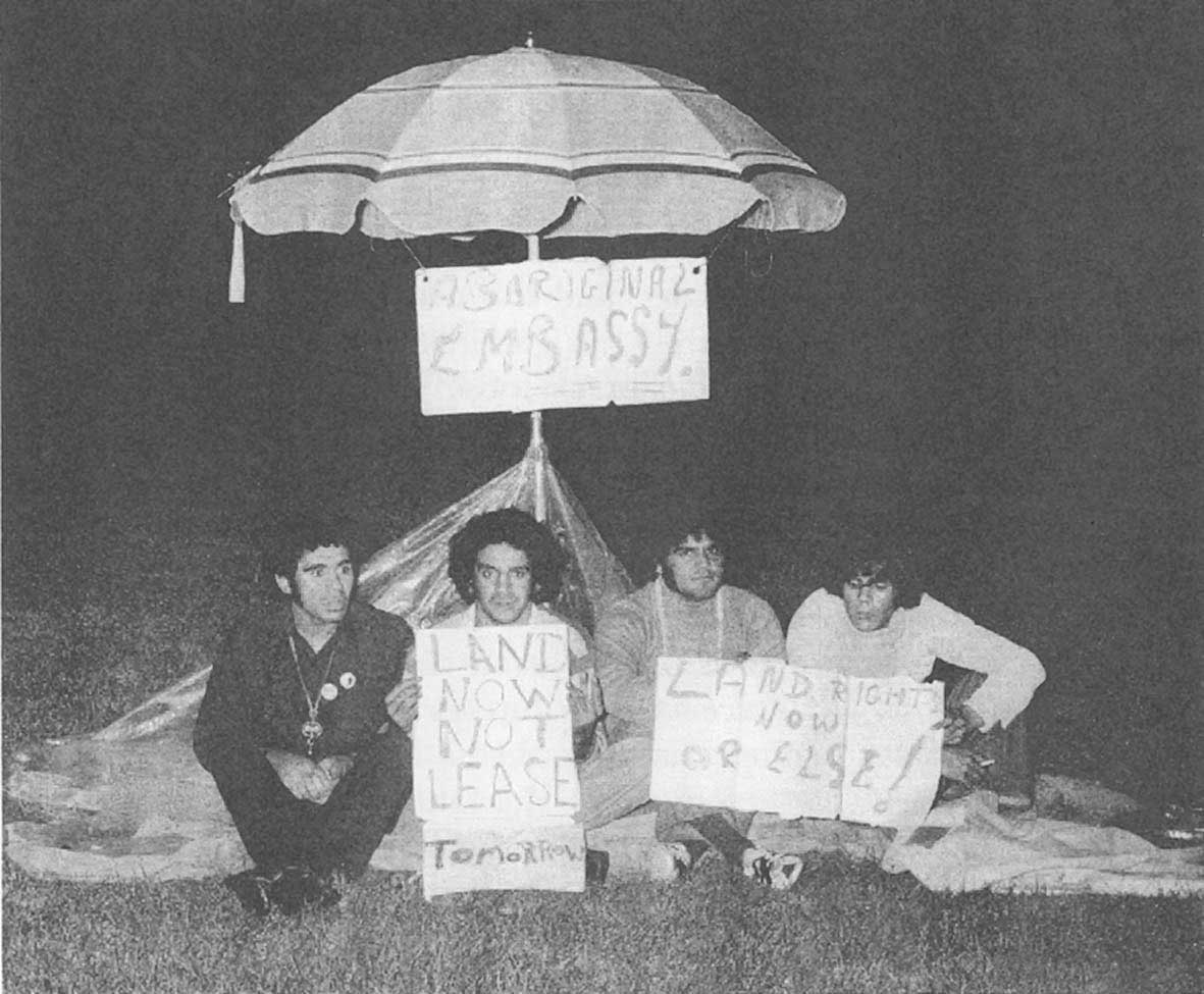 Black and white photo of a group of four male protesters sitting beneath a makeshift embassy fabricated from an umbrella and canvas. They are holding banners and there is a sign fixed to the umbrella that reads: 'ABORIGINAL EMBASSY'.