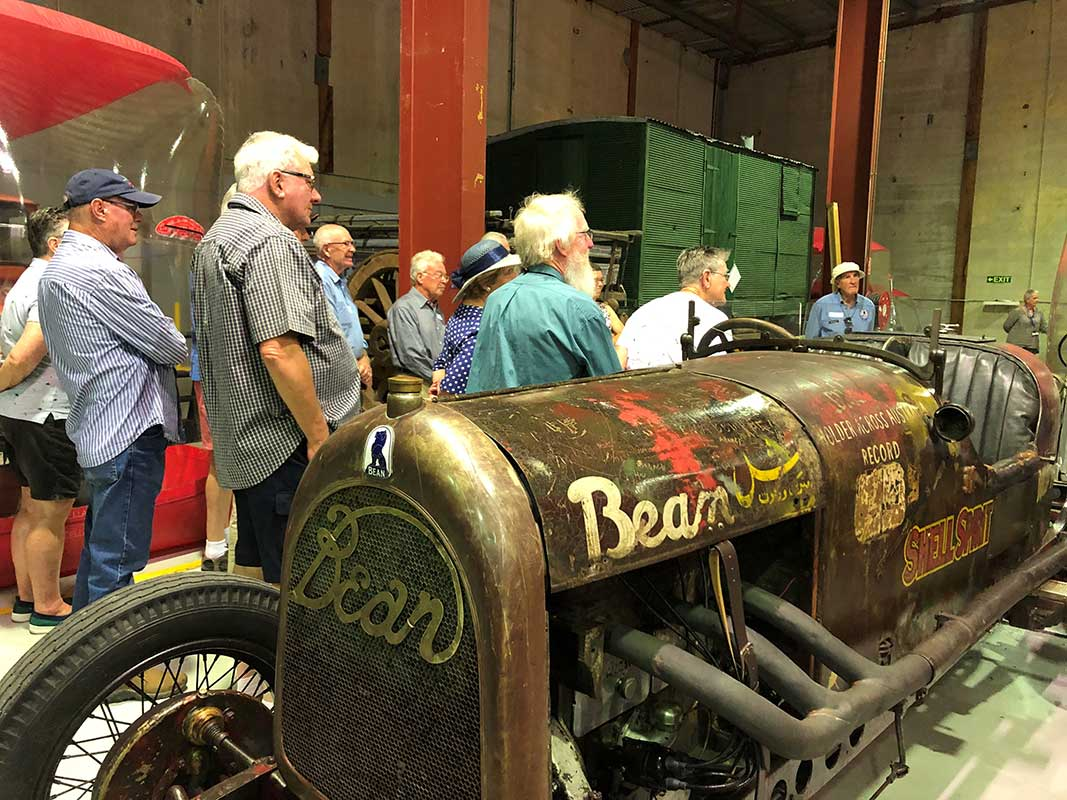 A group of people stand indoors around the historic Birtles Bean car