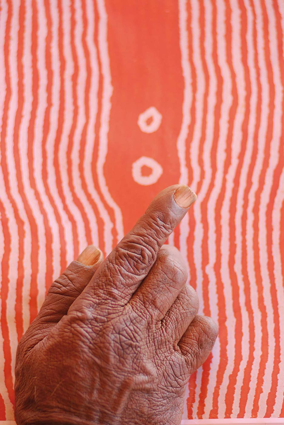 Colour photo of a hand hovering over a painting. - click to view larger image
