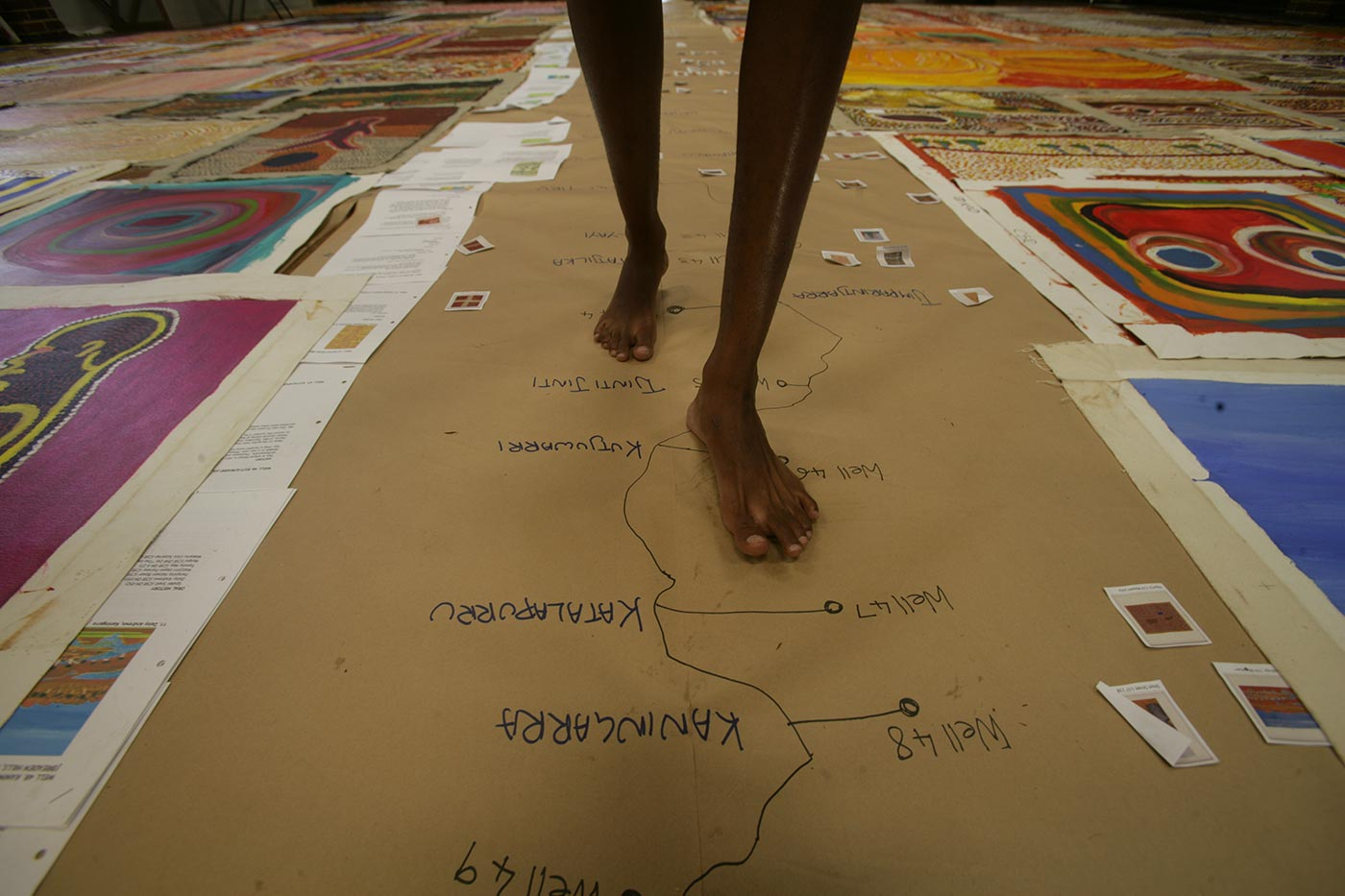 Colour photograph of bare feet walking across an image of a map route on the floor.