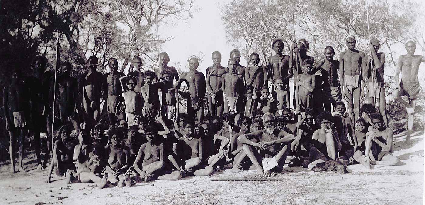 Black and white photo of a group photo of a large group of people in bushland. Some are holding spears.