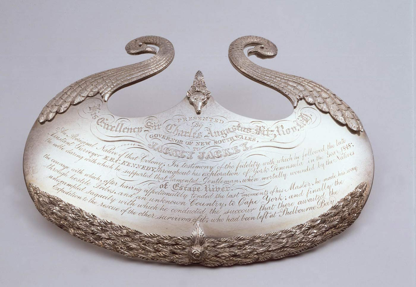 Silver gorget with ornate engraved design and text.