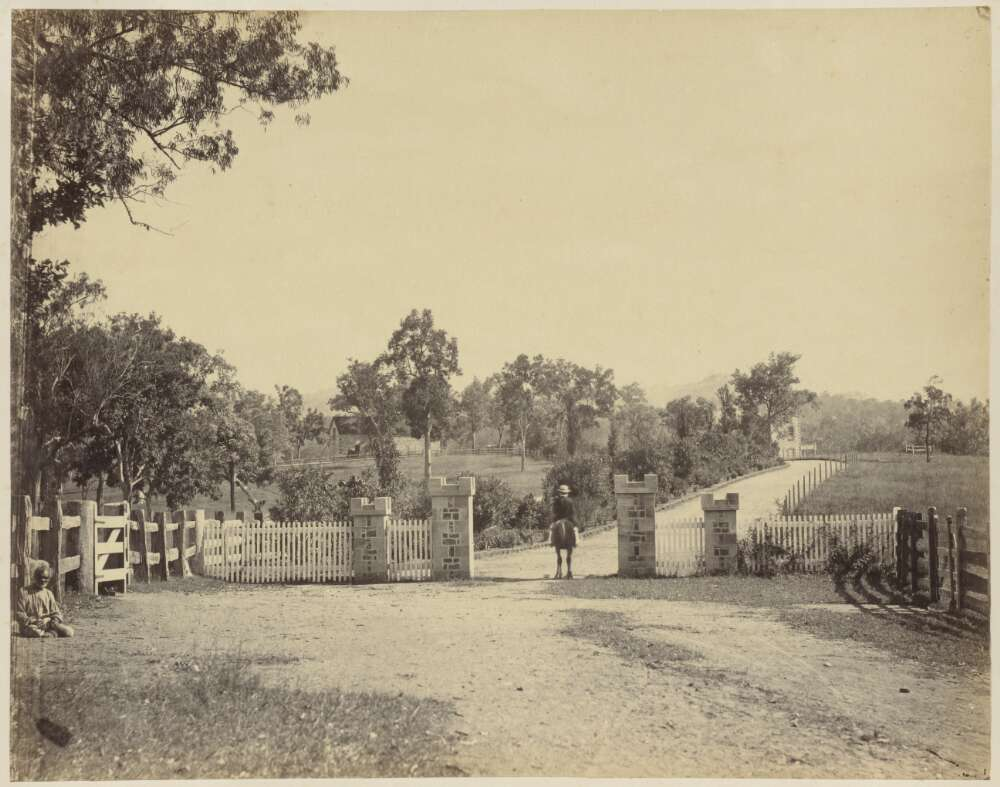 Black and white photograph showing an entrance to an estate.