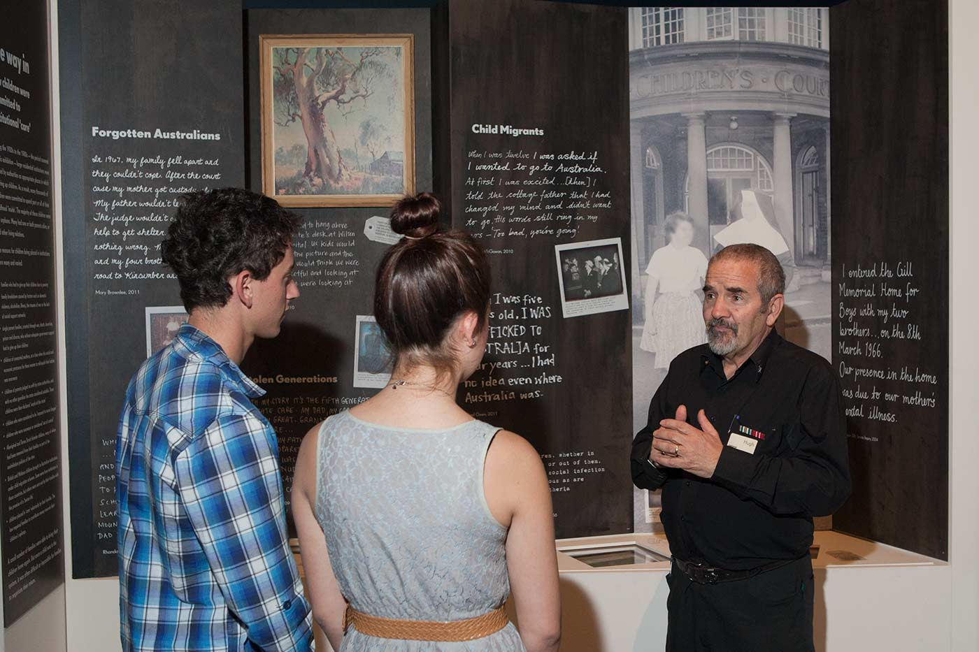 Colour photograph showing a man standing in front of a museum display. Two young people, their backs to the camera, talk with the man. - click to view larger image