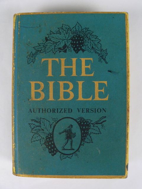 An image of the front of a hardcover book with a blue cover and yellow edging. 'THE BIBLE' is printed in yellow on it with 'AUTHORIZED VERSION' printed in black below. A design of grapes and grape leaves as well as a man sowing grain are also printed in black. - click to view larger image