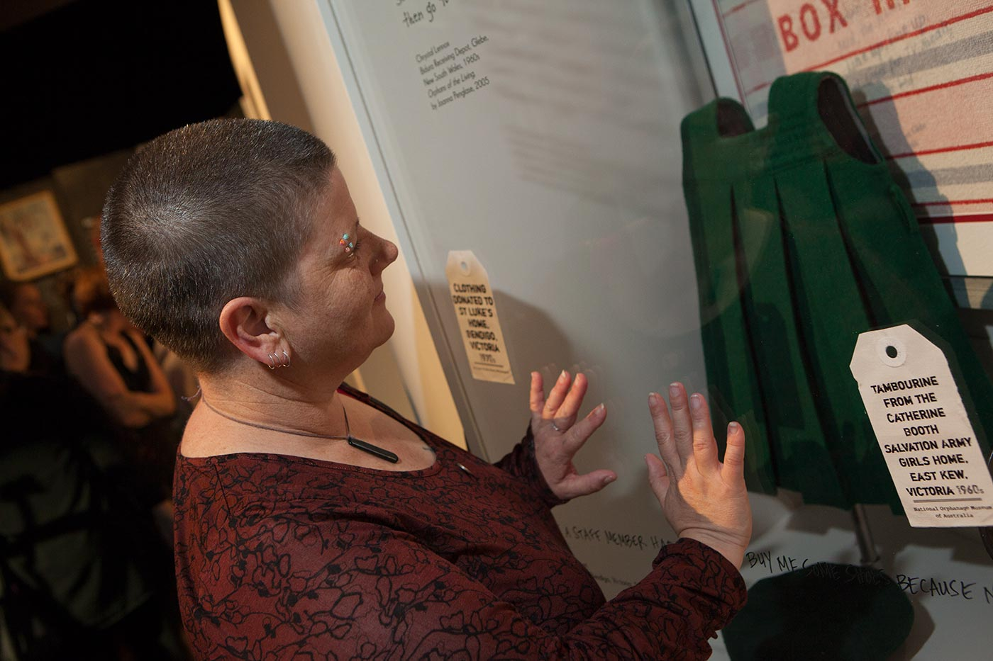 A woman presses her hands against a glass case displaying a child's dark green school tunic. - click to view larger image