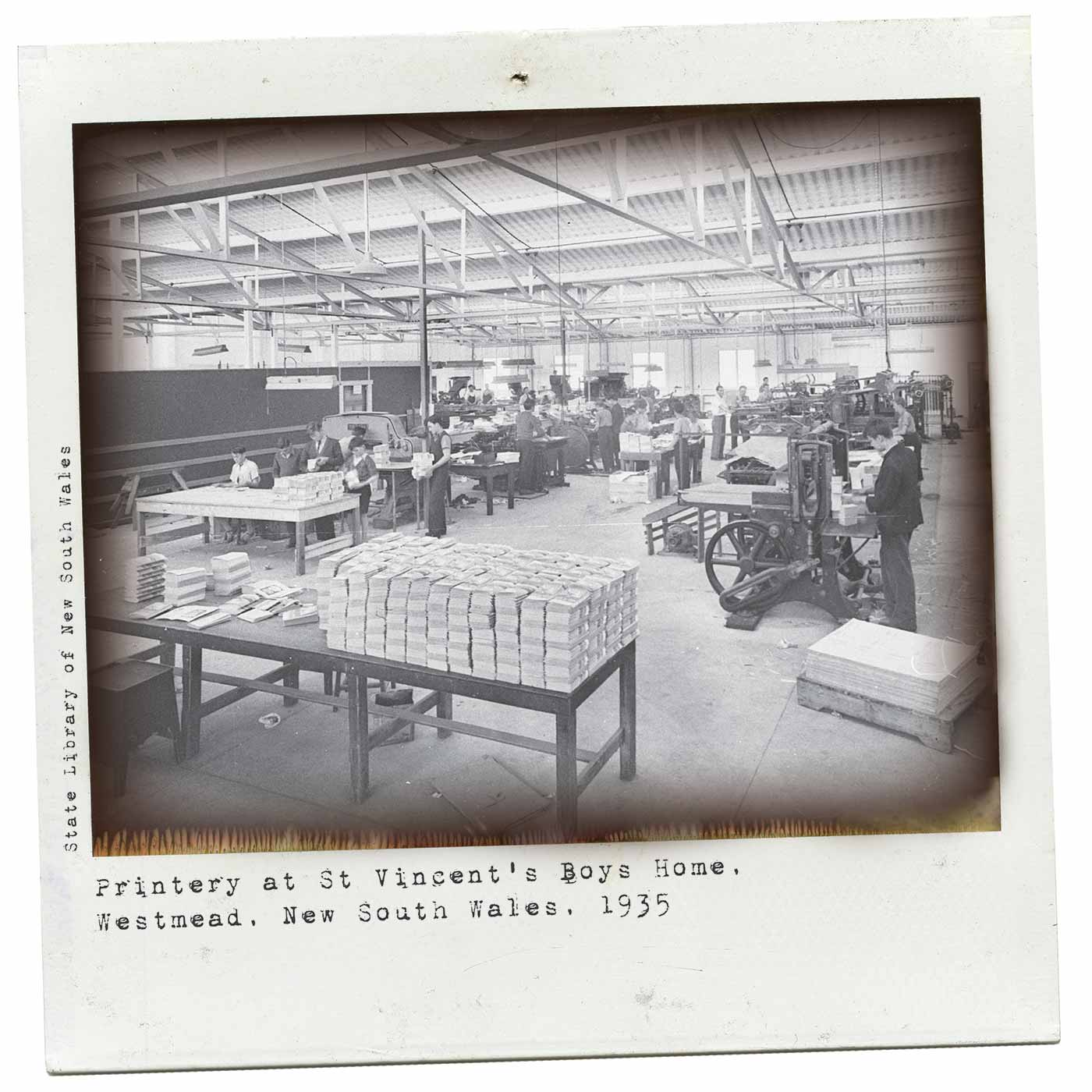 Polaroid photograph showing a large factory floor with various boys working machinery and stacking papers. Typewritten text below reads 'Printery at St Vincent's Boys Home, Westmead, New South Wales, 1935'. 'State Library of New South Wales' is typed along the left side. - click to view larger image