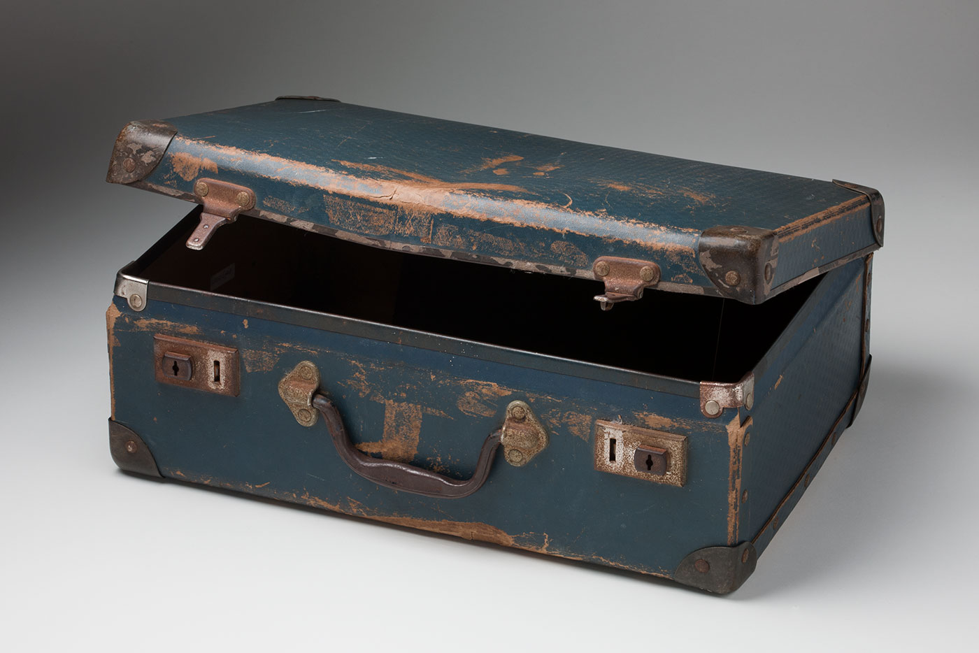 Photograph of a small blue suitcase with reinforced corners, metal locks and a worn black handle. The lid is partially open. - click to view larger image
