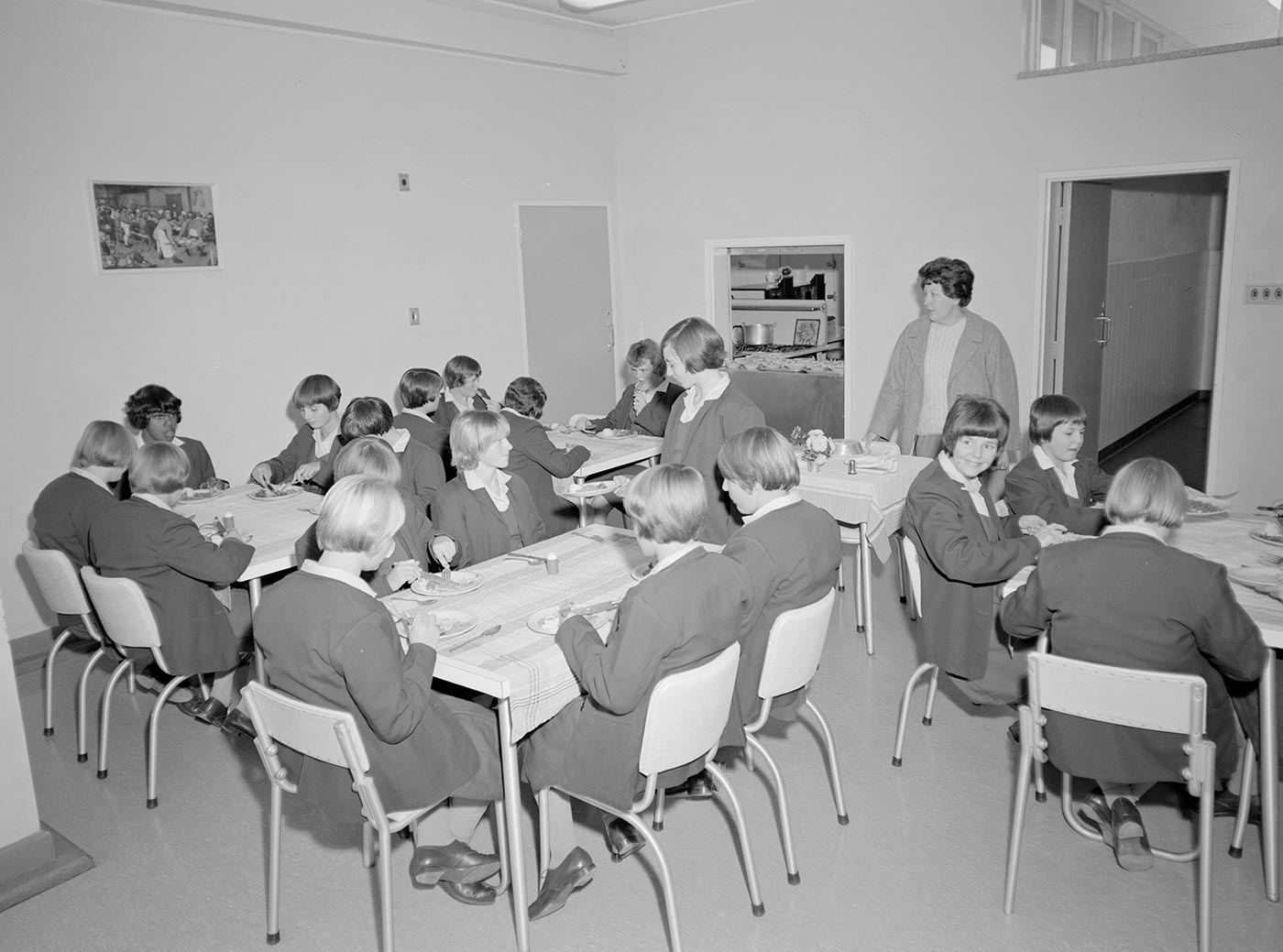 Black and white photo showing groups of teenage girls seated at various sized tables. The girls wear a uniform and are being supervised by a woman who stands at the centre of the image. - click to view larger image