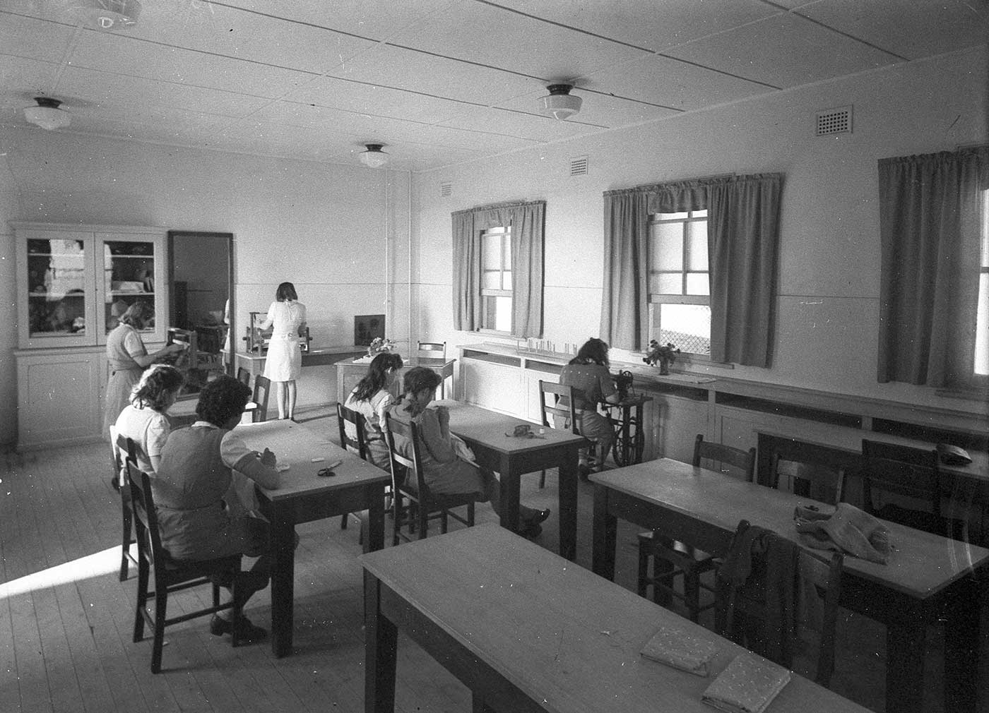 Black and white photo showing seven girls at work in a classroom. The girls have their backs to the camera. Four are seated at desks, one sits at a trundle sewing machine and another two are standing operating machines at the far end of the room. - click to view larger image