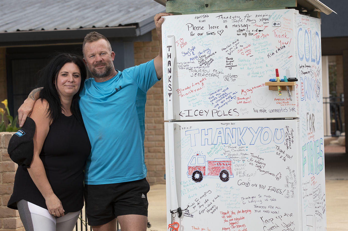 A woman and man stand beside a fridge decorated with messages of support for firefighters.