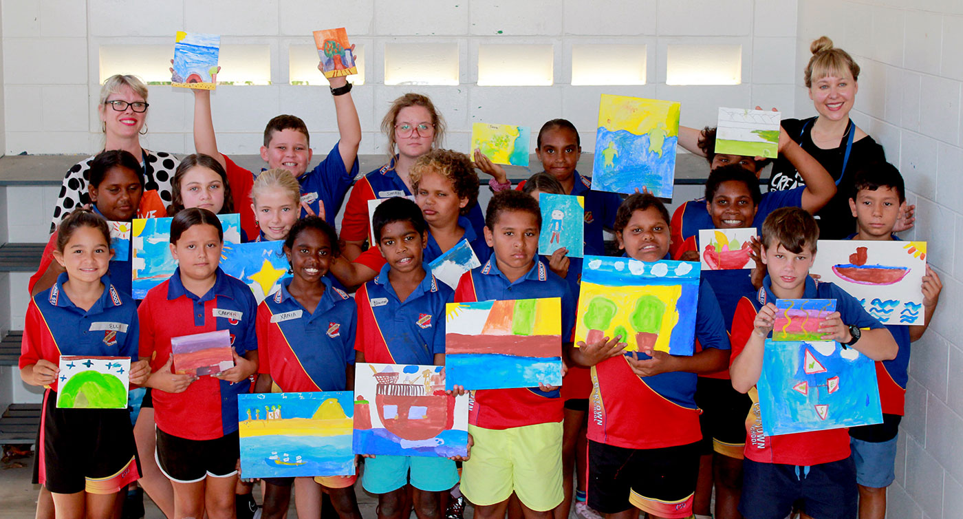 Group shot of primary school students and teachers display their finished paintings.