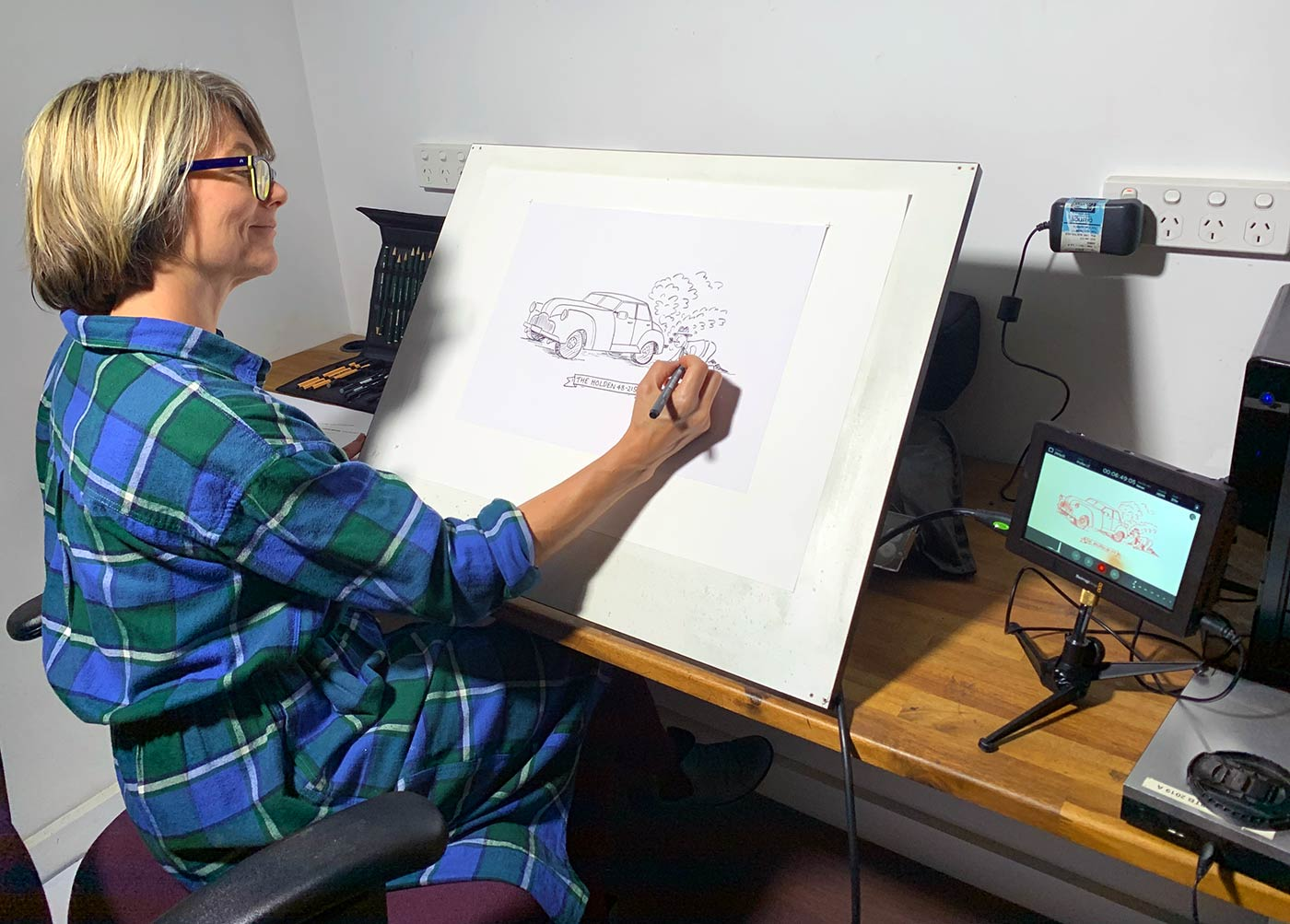 A woman sits at a studio desk sketching an animation using digital equipment.