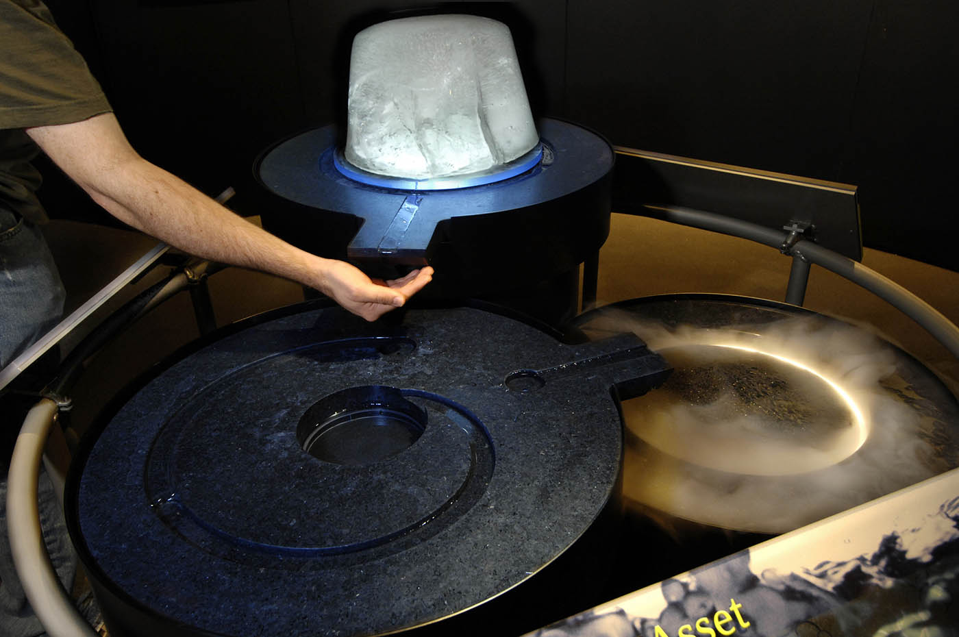 An arm extends into a stream of water coming from a block of ice, mounted on a circular plinth. Below the ice block, water spirals around the top of another plinth, which flows into a third plinth where a whitish vapour rises from the centre.