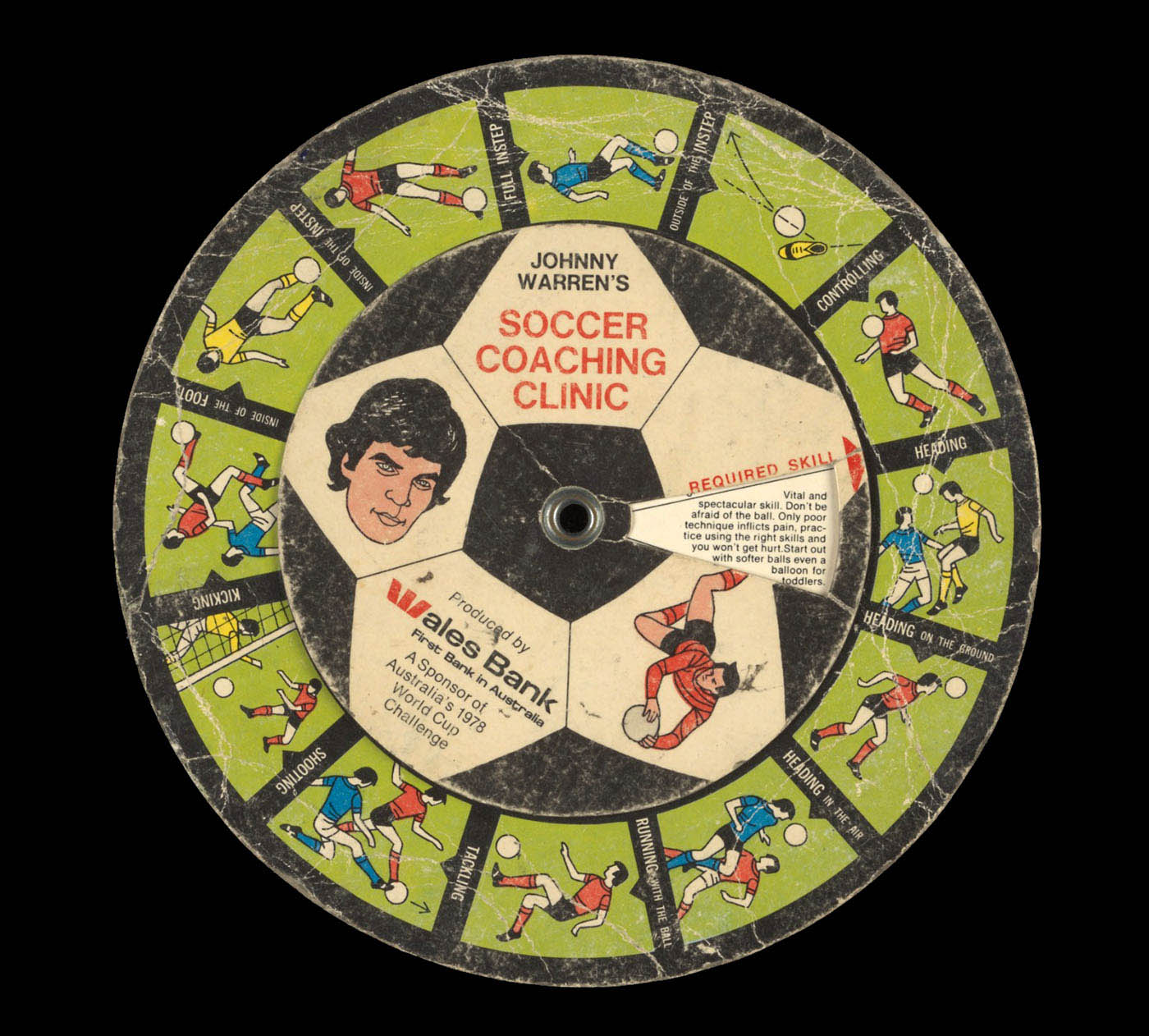 A colour printed cardboard disc with illustrations of football players in different positions, and accompanying descriptive text. There is an illustrated portrait of John Warren at the centre with text 'JOHNNY / WARREN'S SOCCER / COACHING / CLINIC / Produced by / Wales Bank / First Bank in Australia / A Sponsor of / Australia's 1978 / World Cup / Challenge'. - click to view larger image