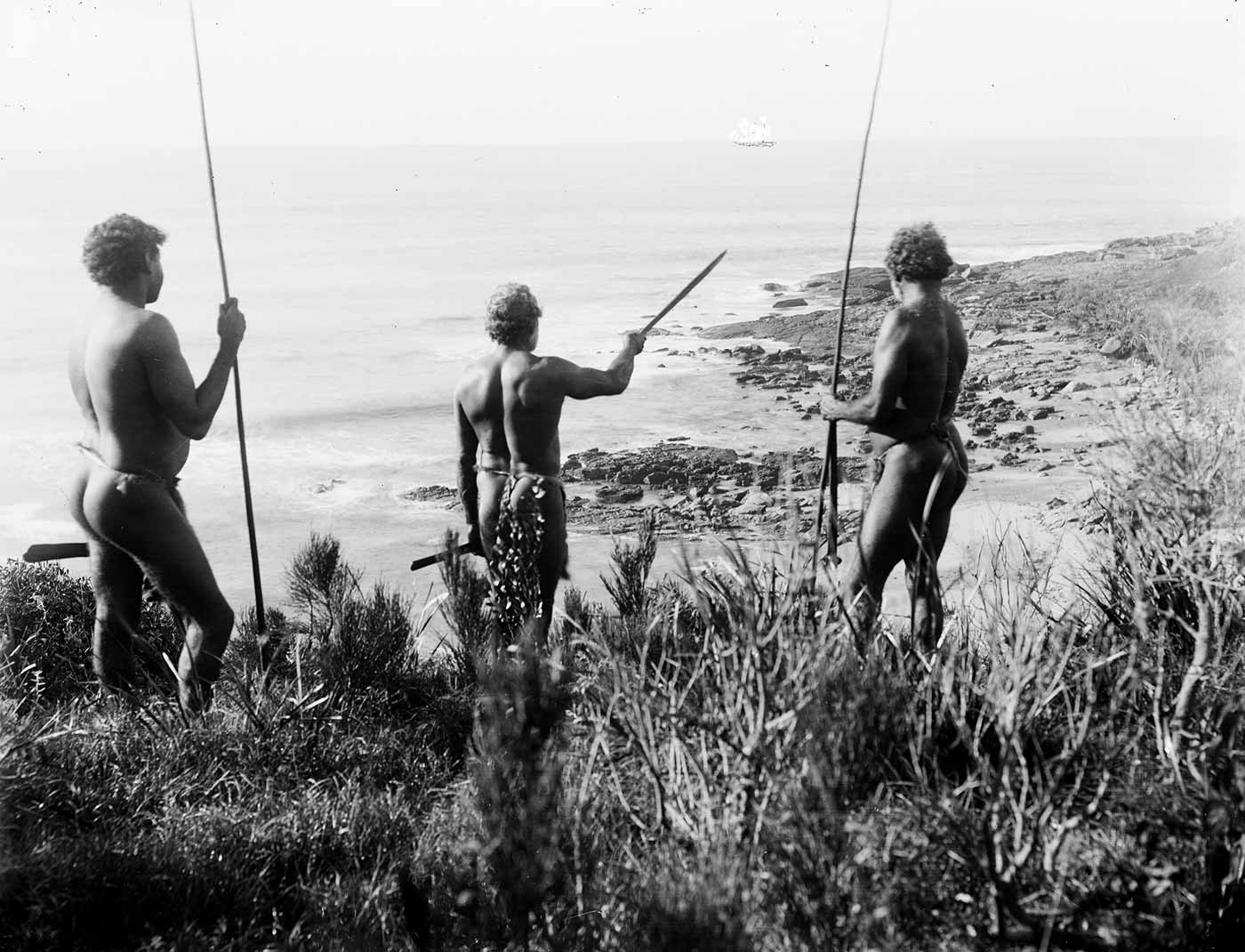 Black and white photograph of three men with spears overlooking a rocky beach with a sailing ship on the horizon. One man is indicating with his spear towards the ship. - click to view larger image