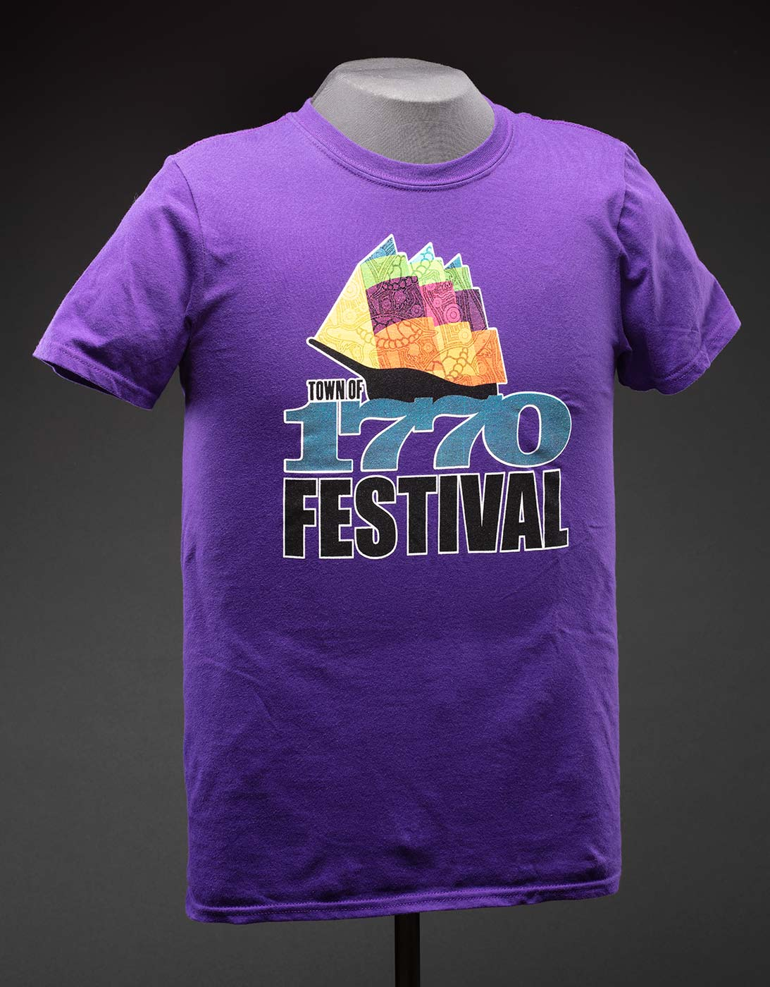 A purple T-shirt with a logo on the front that features a colourful, abstract design of a sailing ship with an indigenous design. Below the illustration is text that reads 'TOWN OF / 1770 / FESTIVAL'.