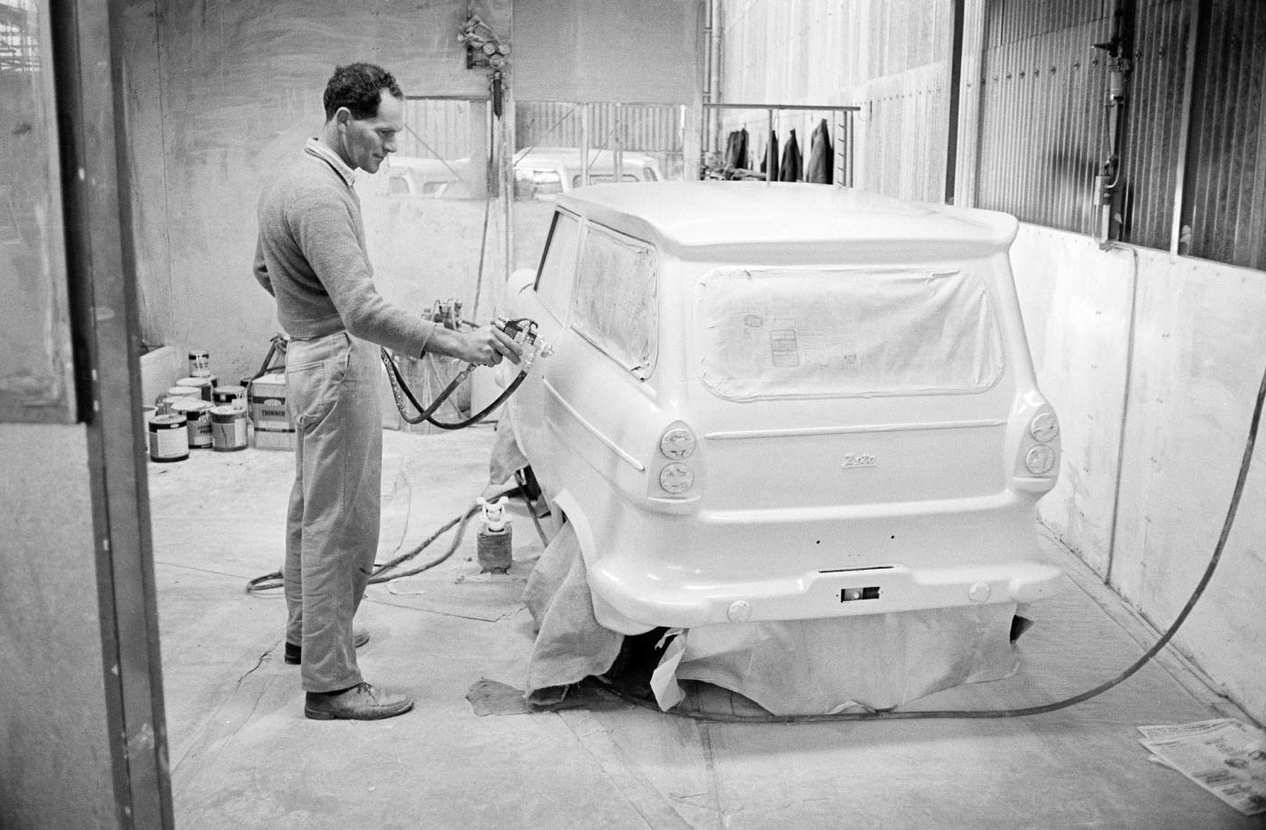 A black and white image of a worker facing a small white car body. - click to view larger image