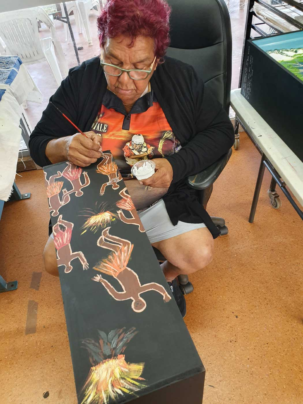 Colour photo of an elderly woman sitting in a chair and painting images of people onto a canvas. - click to view larger image